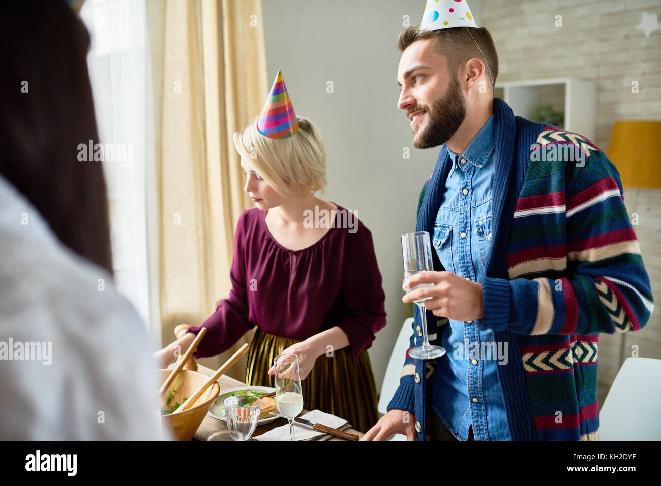 Group of happy young people wearing holiday caps celebrating Birthday with friends holding champagne glasses during - Stock Image