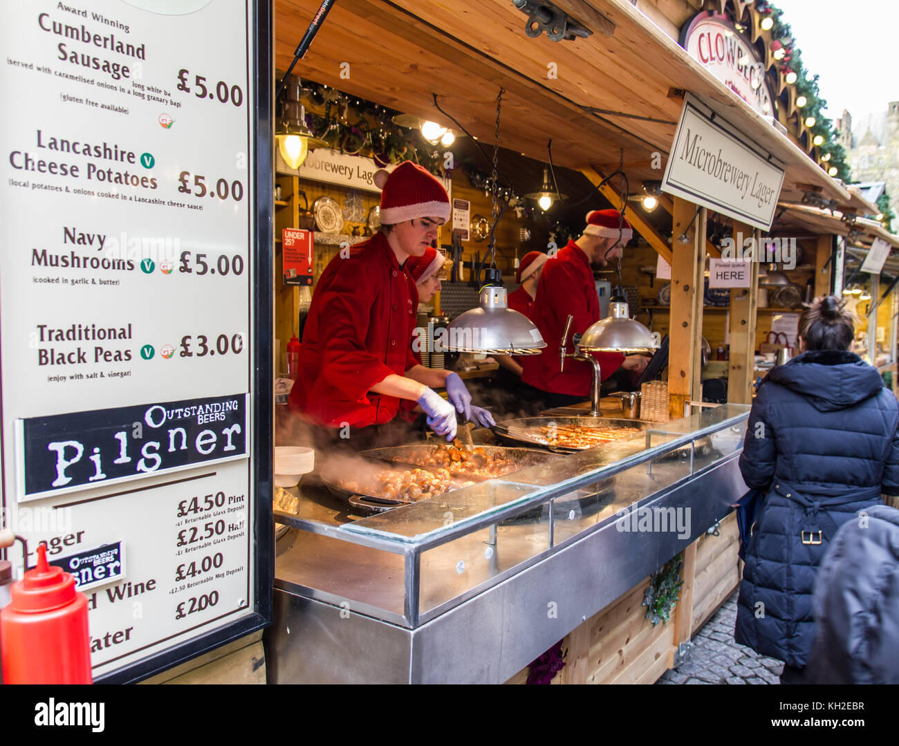 Food stall with staff  preparing food for customers at the Manchester Christmas Market on Albert Square, UK taken - Stock Image