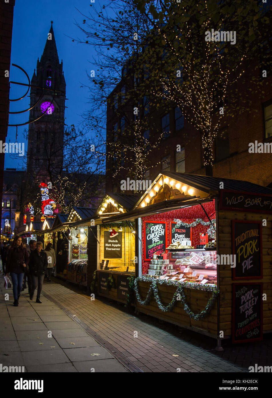Christmas Market Stalls at the top of Brazennose street, Manchester, UK and town hall clock in the background - Stock Image
