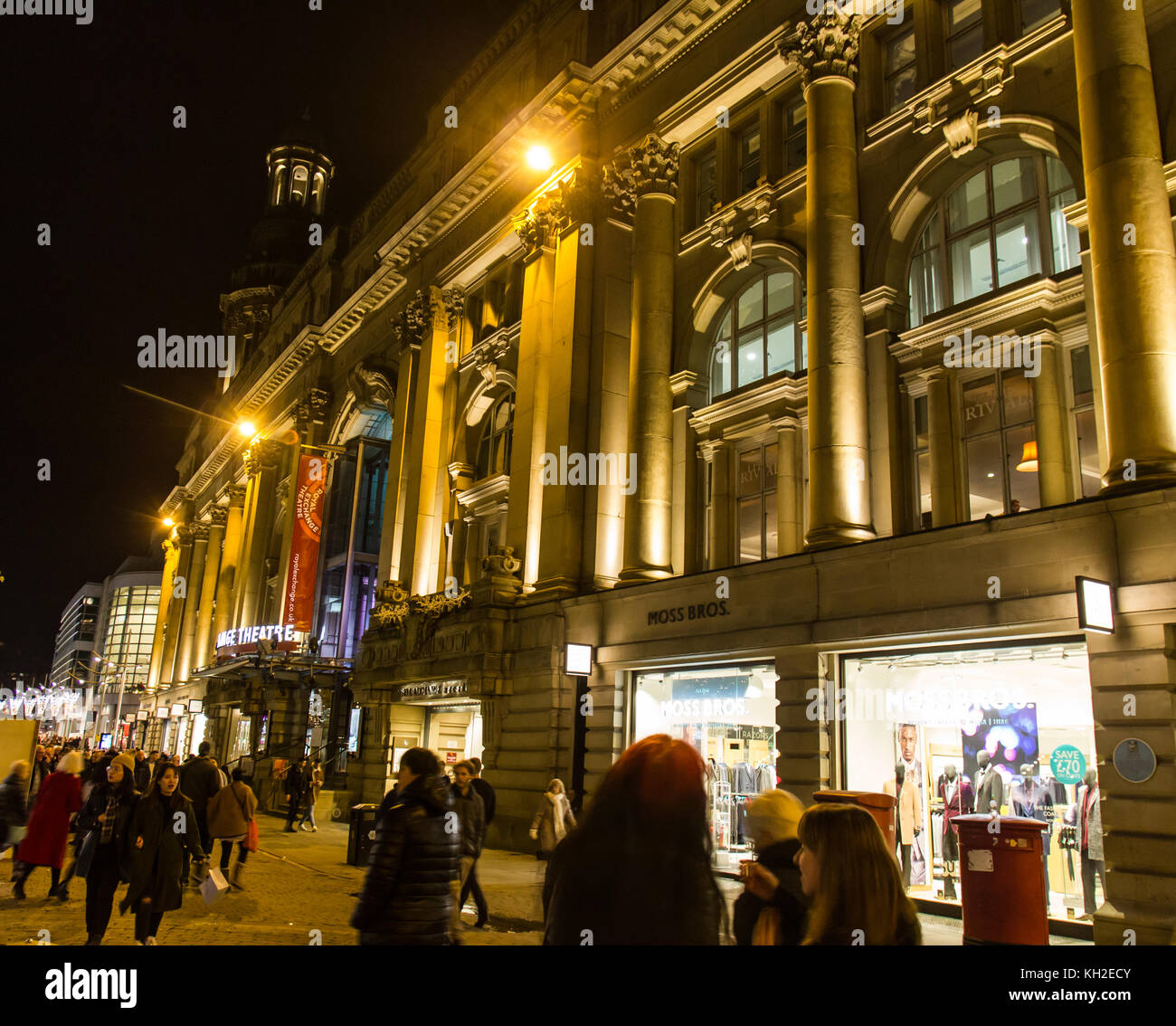 Manchester Royal Exchange Theatre building lit up at night  with shops and shoppers on St Annes Square, Manchester, - Stock Image