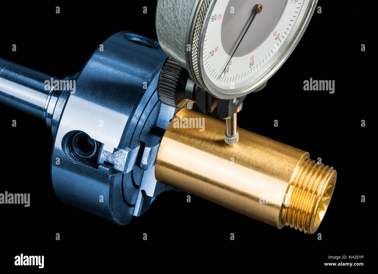 Tolerance measurement of brass workpiece in chuck. Gold fitting in clamp jaw and dial indicator on black background. - Stock Image