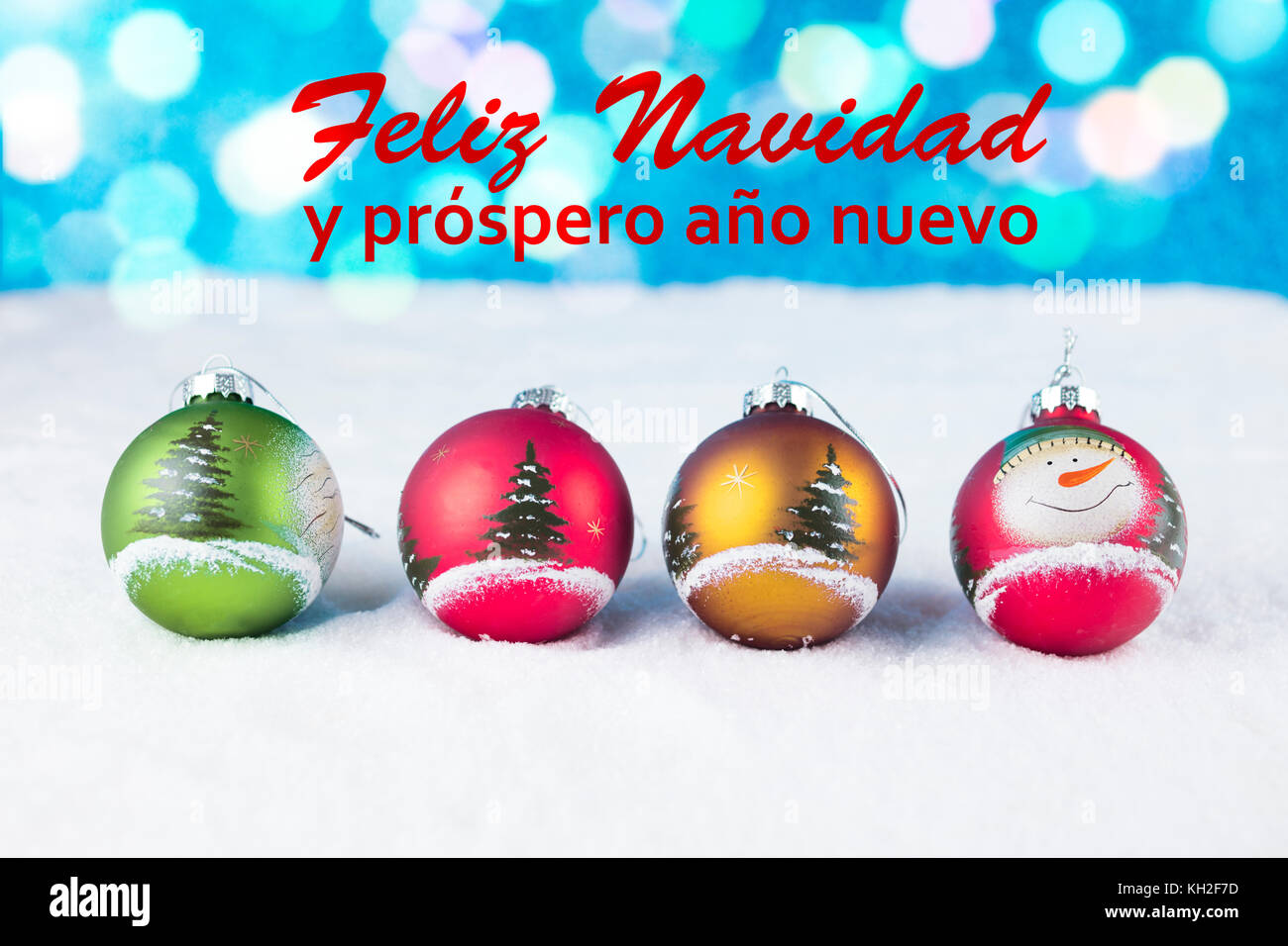 Group of colorful Christmas balls with text in Spanish 'Feliz Navidad y prospero año nuevo' in white - Stock Image