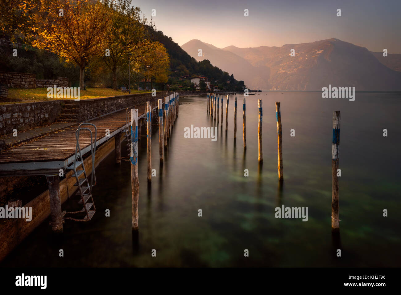 Little harbour on Iseo Lake with mountains in background, Italy - Stock Image