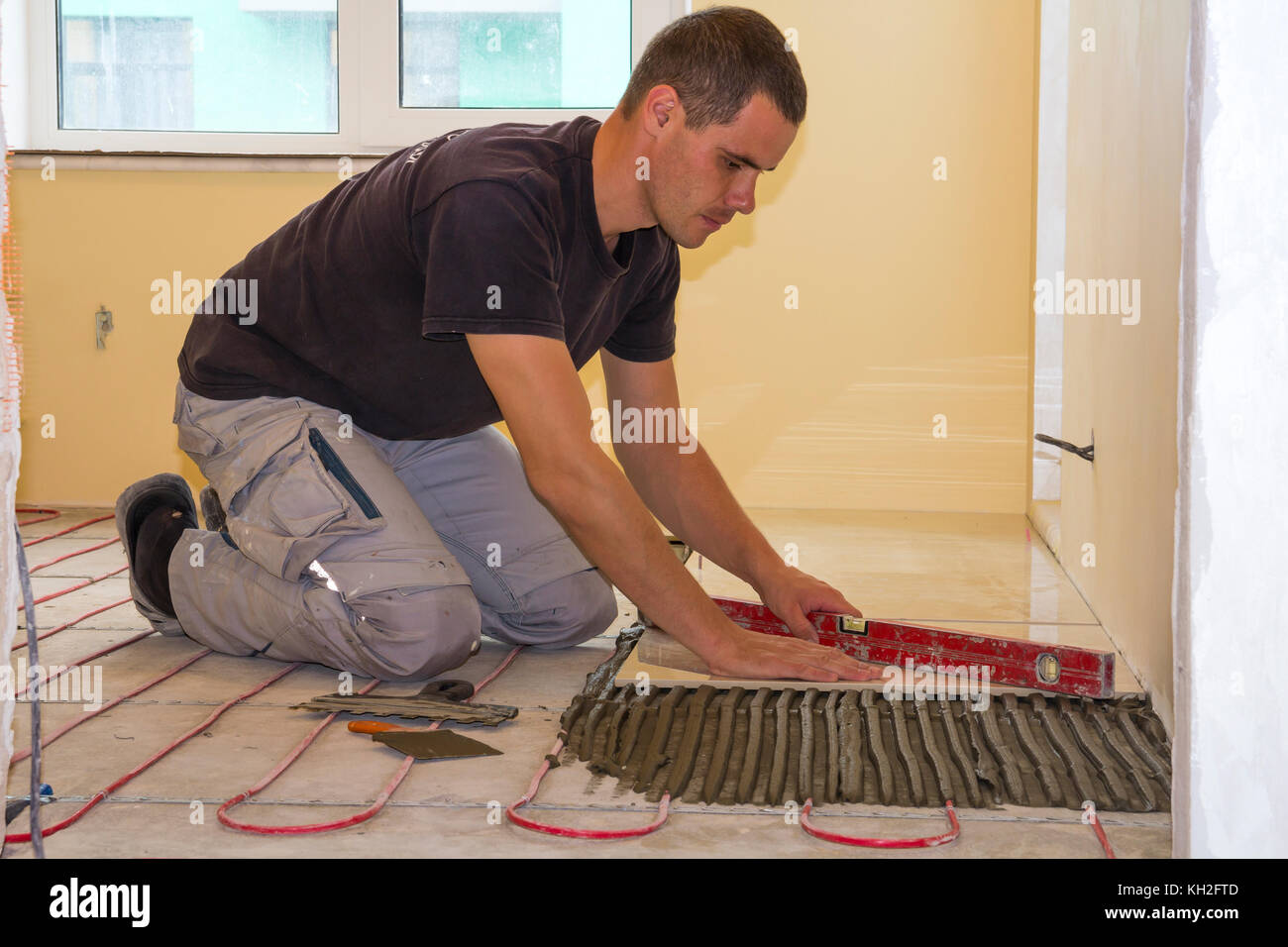 Worker installing floor tiles  Ceramic tiles and tools for
