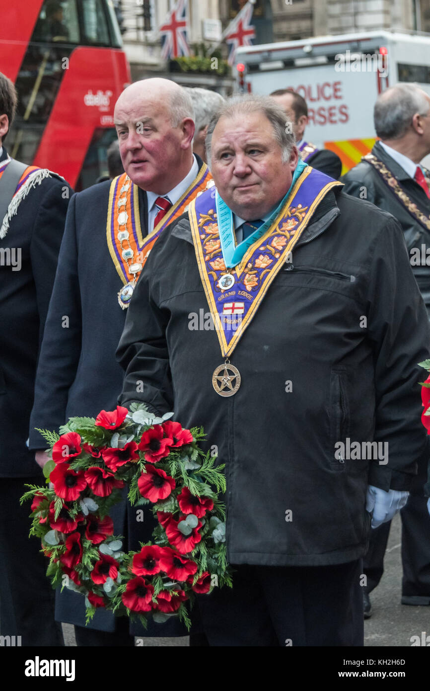 London, UK. 11th November 2017. A man with a Grand Lodge of England sash waits with a wreath on the London City - Stock Image