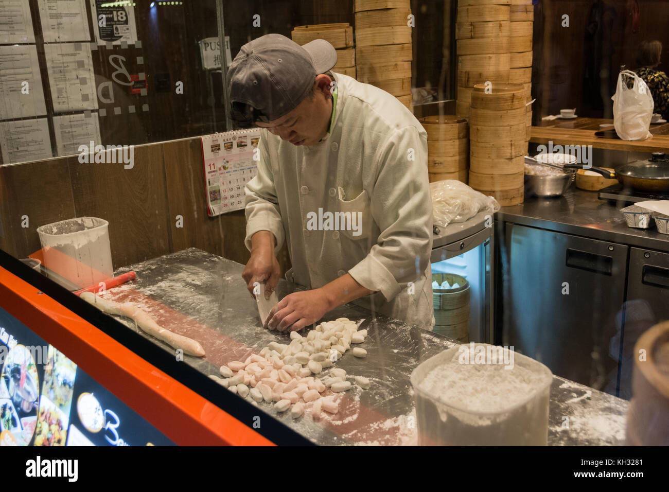 A young Chinese chef rolls Chinese Dim Sum in China Town, London, England, UK. - Stock Image