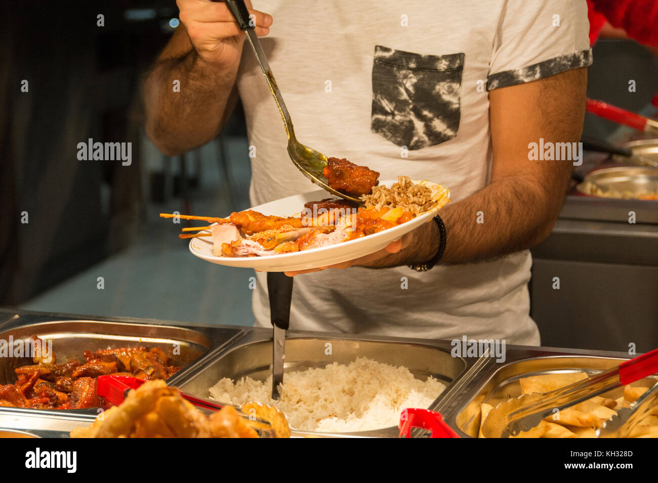 Customers helping themselves to food in a Chinese restaurant in China Town, London, England, UK. - Stock Image