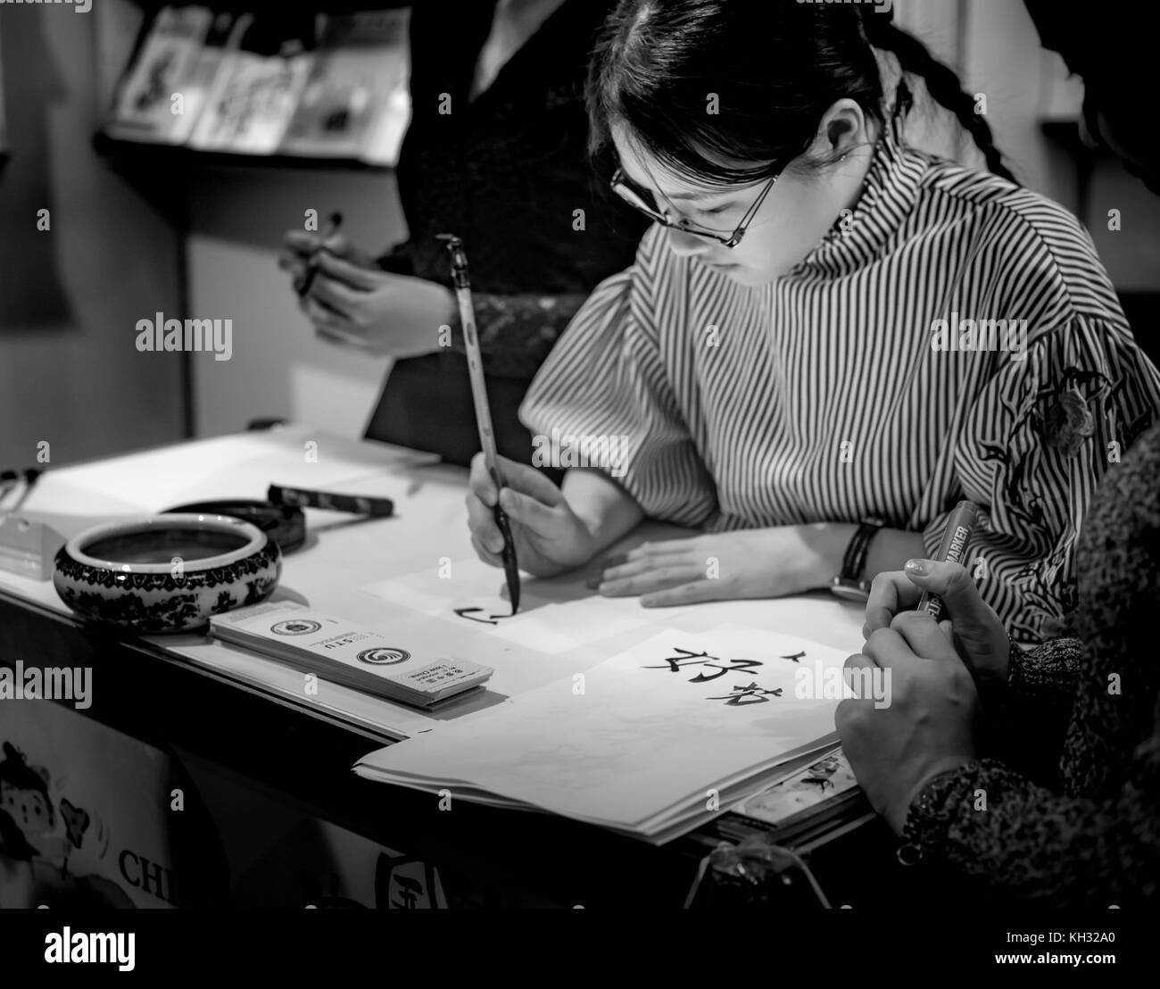 A black and white horizontal image of a Chinese girl writing/drawing calligraphy in a class room. - Stock Image