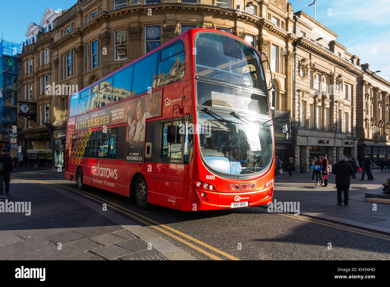 A red double decker bus at speed in Blackett Sreet by Greys Monument pedestrian are in central Newcastle upon Tyne - Stock Image