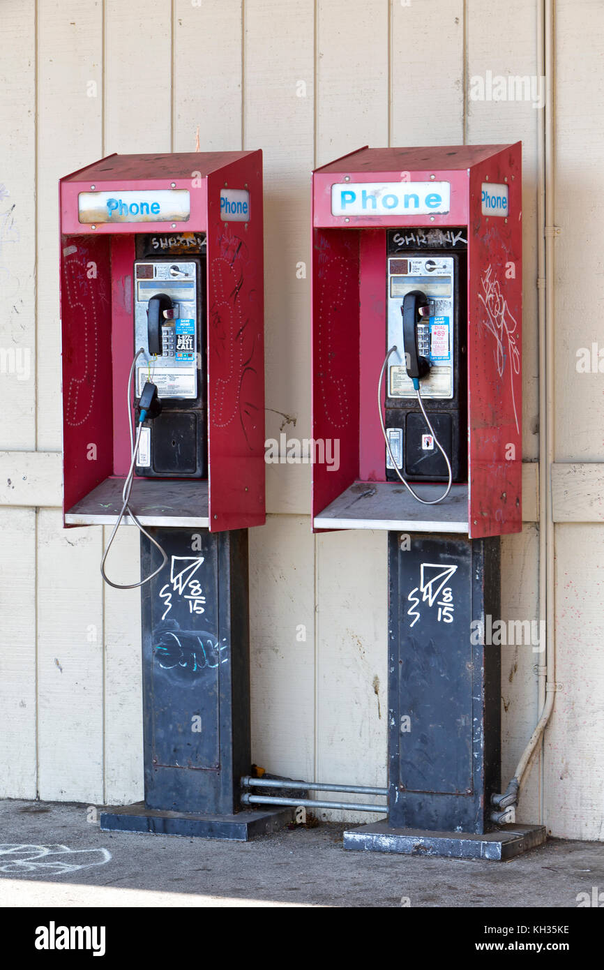Abandoned coin operated public pay telephones with coin release slot, graffiti. - Stock Image