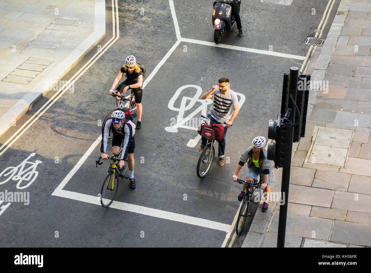 Cyclists waiting at advanced stop line (ASL), advanced stop box, bike box road markings at signalised road junction - Stock Image