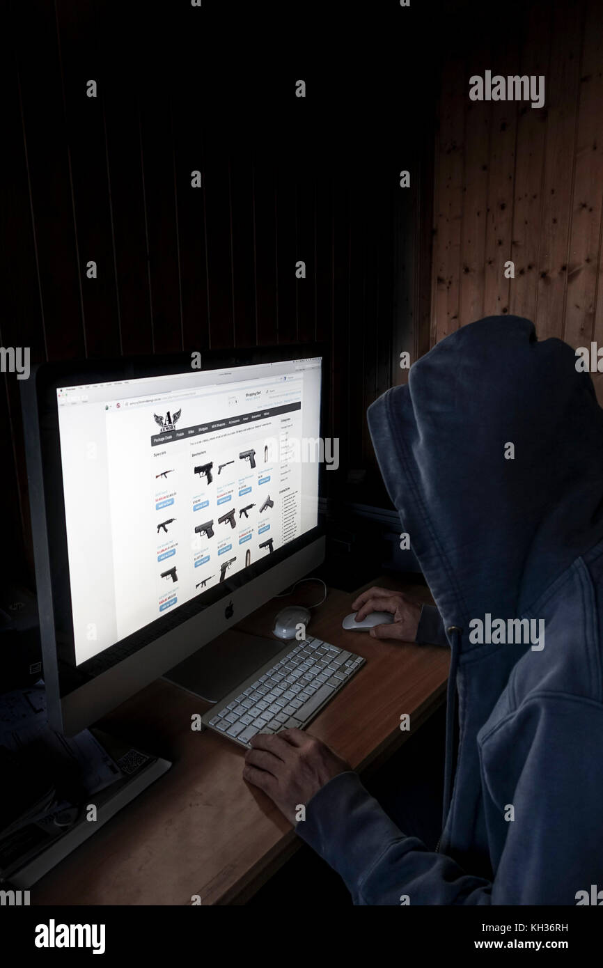 Concept image of Hooded cyber criminal, man using computer to access internet deep web page offering guns, - Stock Image