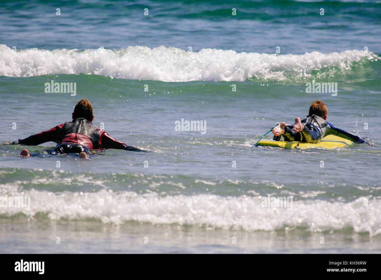 Surfers in the water looking for waves Keel Beach, Achill Island, county Mayo, Ireland - Stock Image
