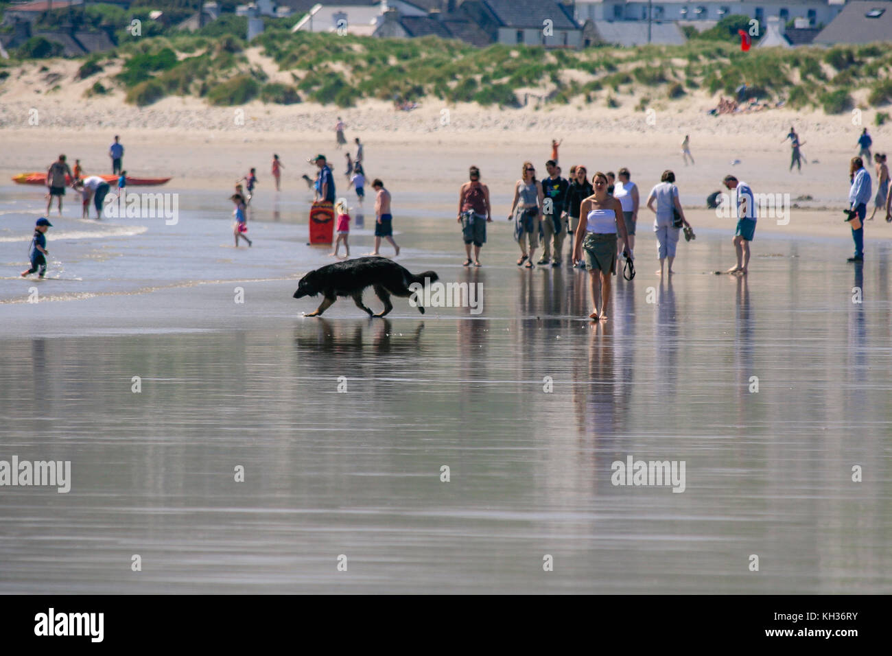 People out on a sandy beach enjoying good weather on a beautiful sunny summer day on a Keel Beach in Achill Island, - Stock Image