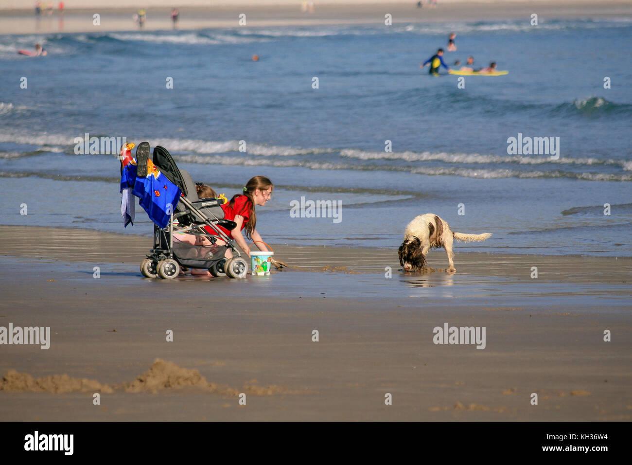 Enjoying good summer sunny weather girl playing with her dog on the Keel beach on Achill Island, Countu Mayo, Ireland - Stock Image