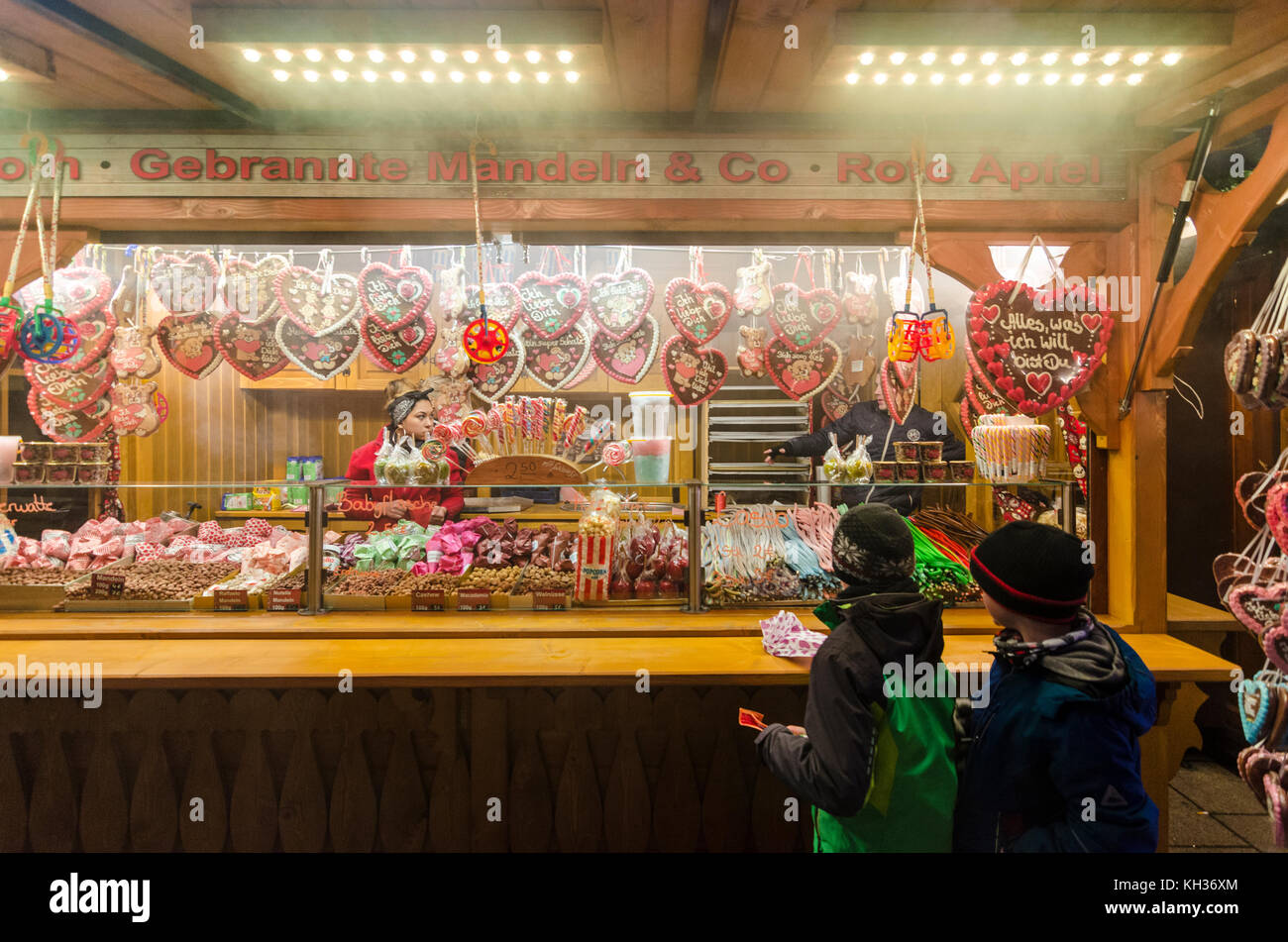 Children buying sweets and candy from a German Christmas Market stall, Berlin, Germany - Stock Image