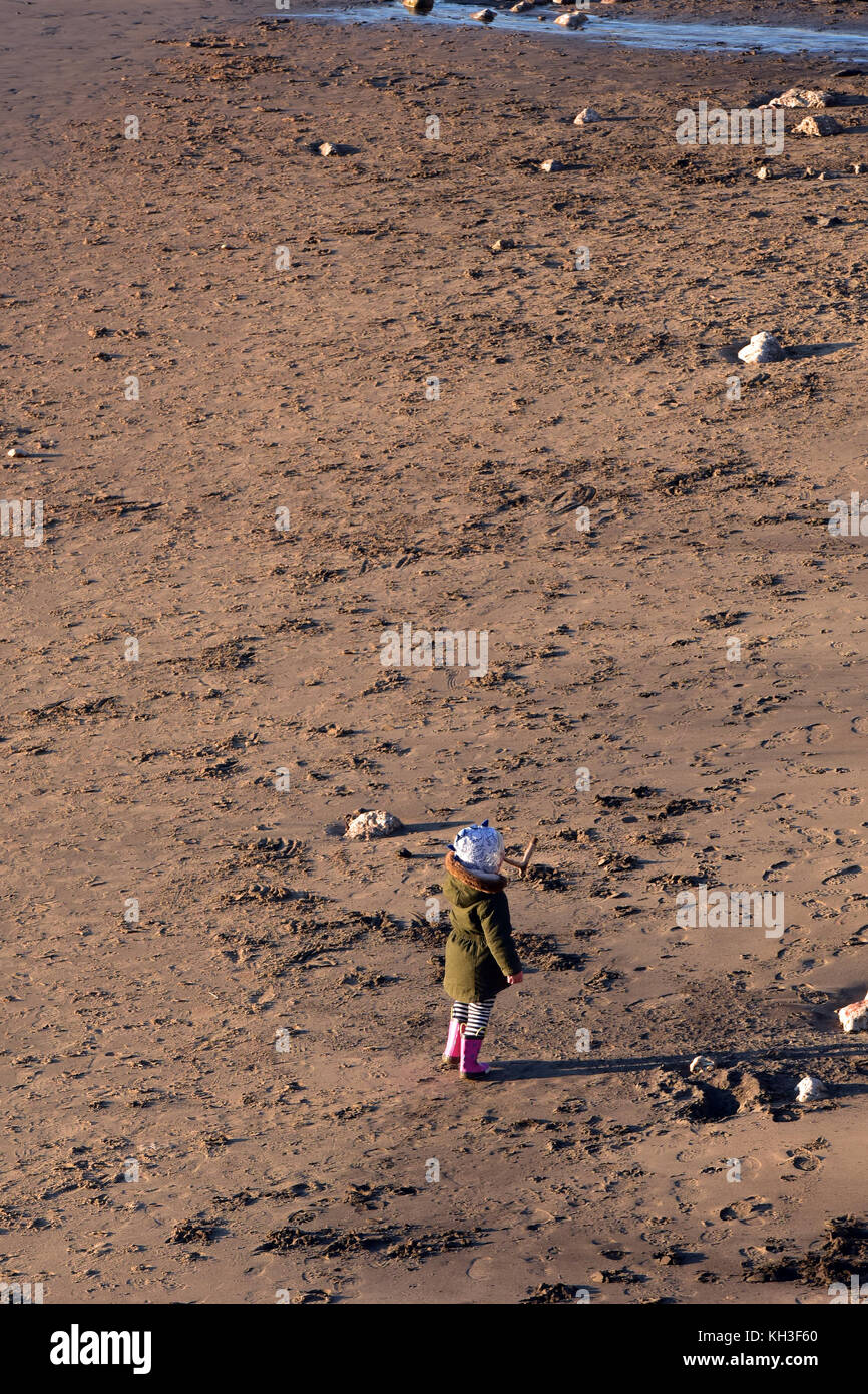 A young child wearing a hat standing on a sandy beach near the sea alone. Abandoned and forgotten and lonely.   - Stock Image