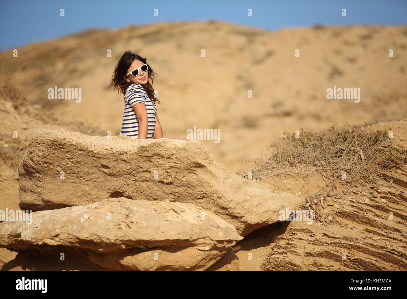 Bat Mitzva young woman is sitting on a sandstone rock on the beach in Israel, posing for her portfolio - Stock Image
