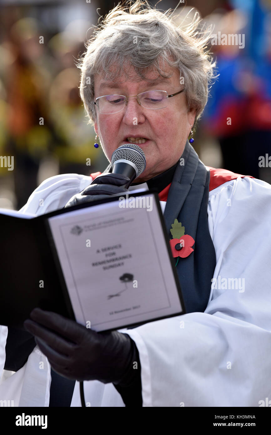 Local Rector delivering a reading on Remembrance Sunday, War Memorial, High Street, Haslemere, Surrey, UK. Sunday - Stock Image