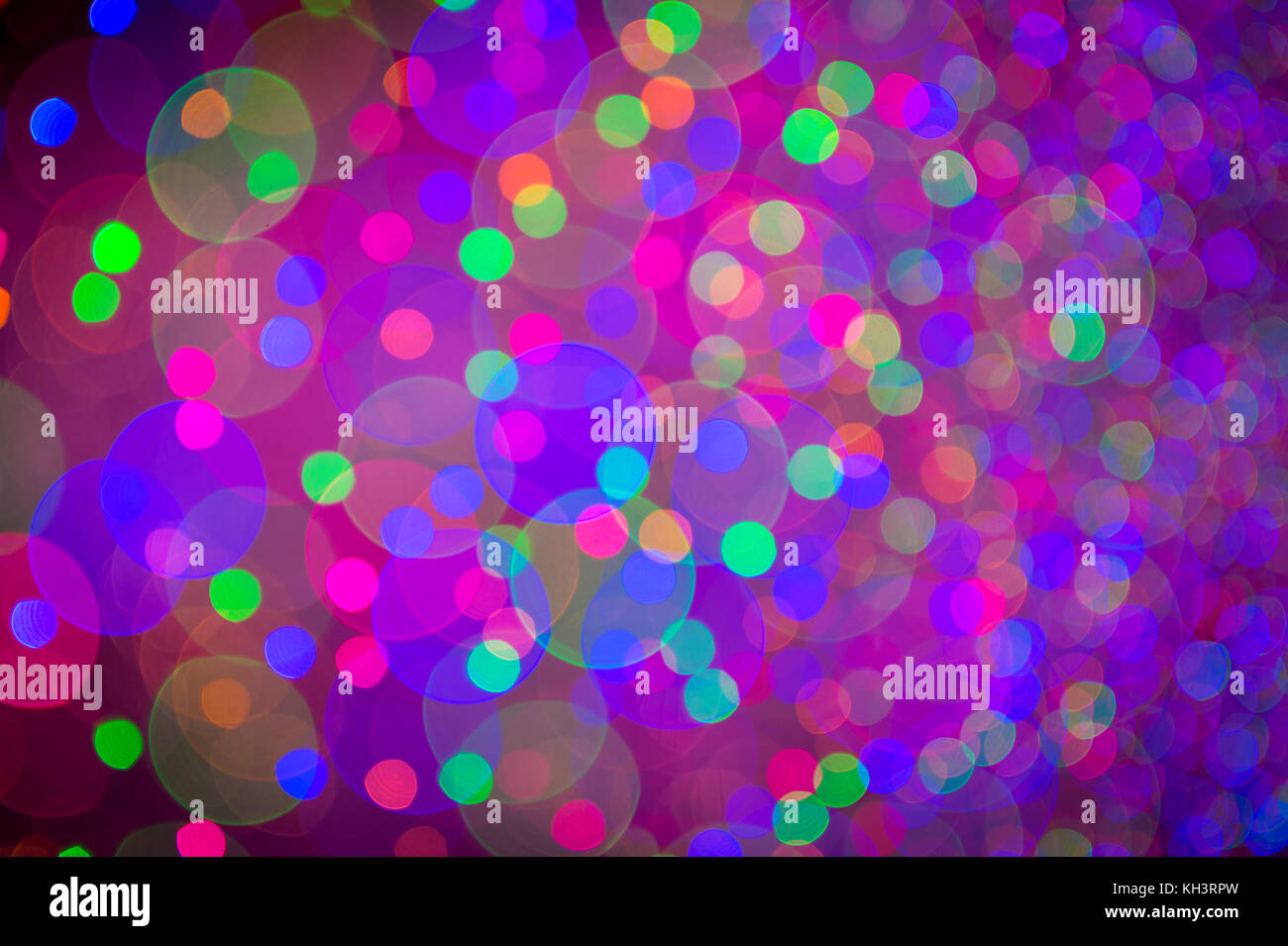 Holiday background in an abstract defocus in vibrant magenta pink bokeh with spots of other colors - Stock Image