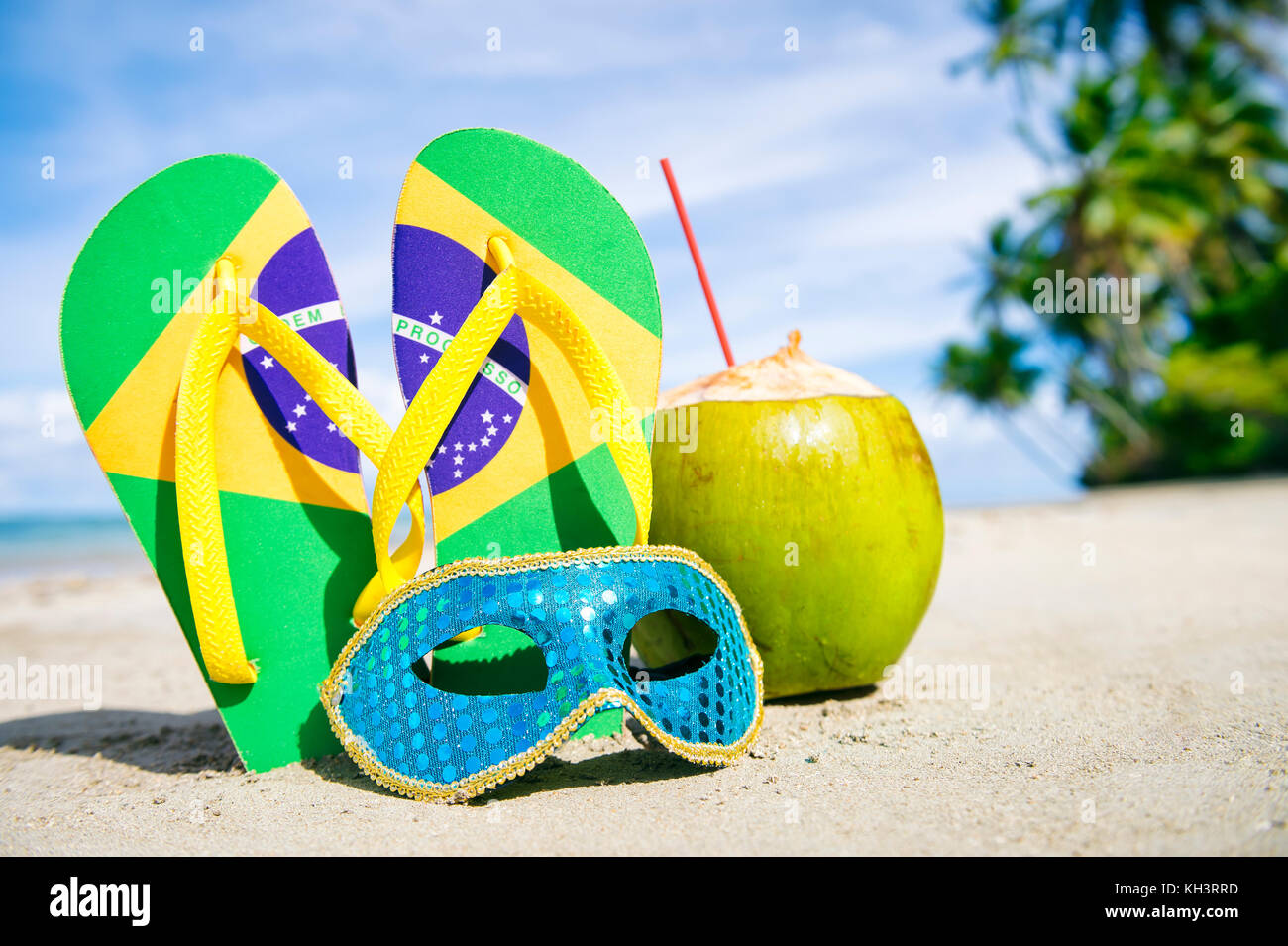 Brazil flag flip flops, colorful sequined carnival mask and fresh green coconut drink on a tropical palm fringed - Stock Image