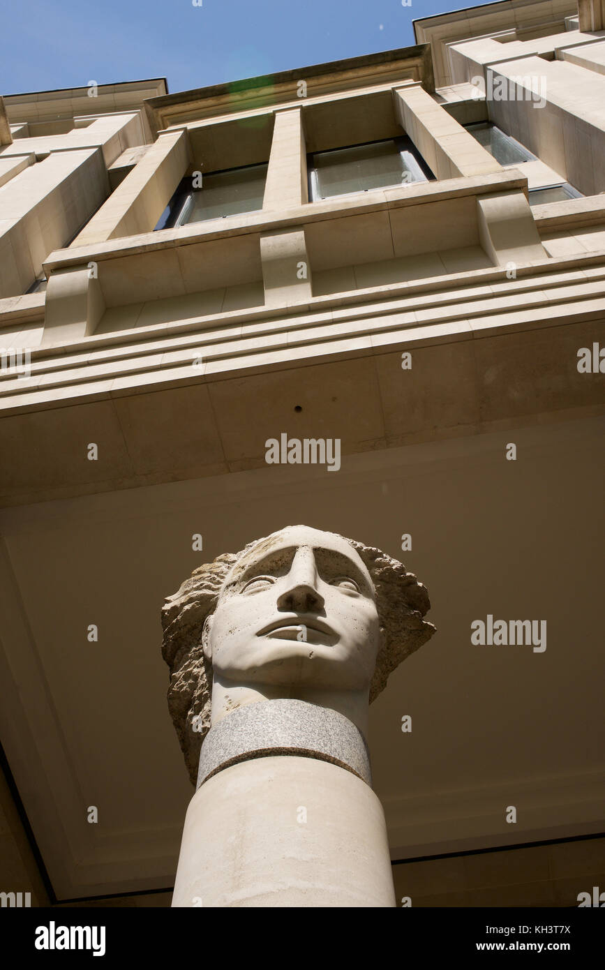 Contrast between classic stone pillars with statue heads and modern building in London - Stock Image