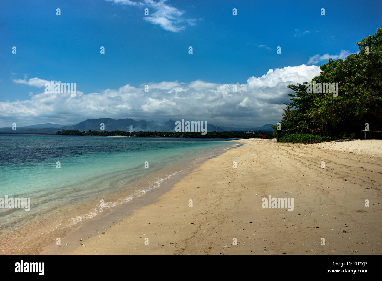 Beach with Ocean and Trees blue sky and Clouds Lombok - Stock Image