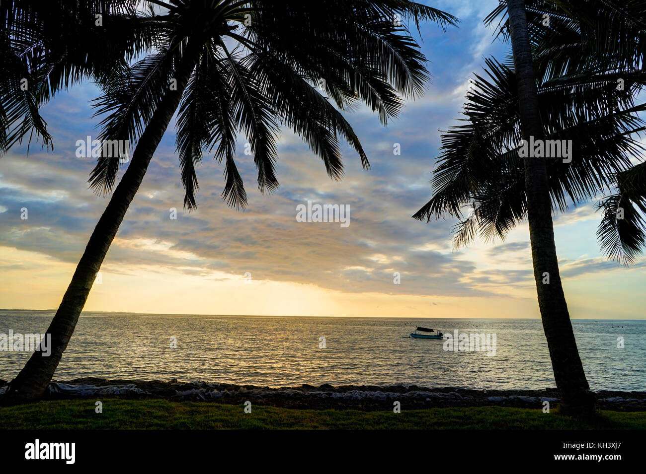 Sunset with Beach palm Trees blue sky and Clouds Lombok - Stock Image