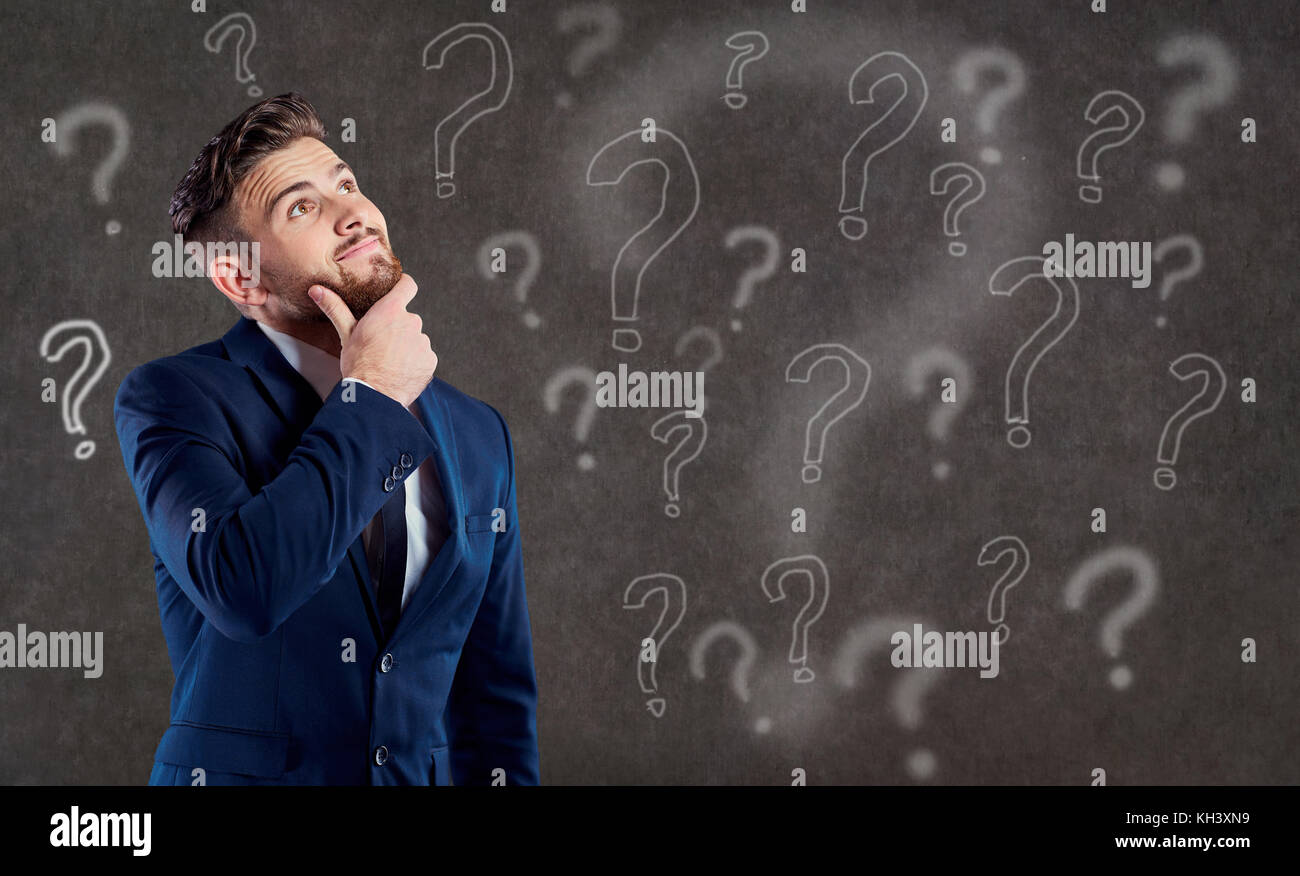 A man in a suit is thinking over a question. - Stock Image