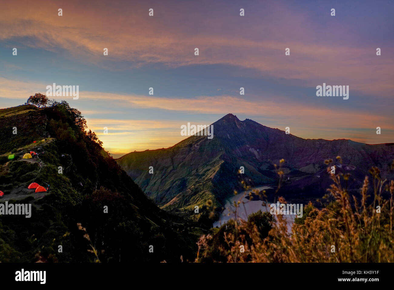 Sunrise Mount Rinjani vulcano with tents Lombok Indonesia - Stock Image
