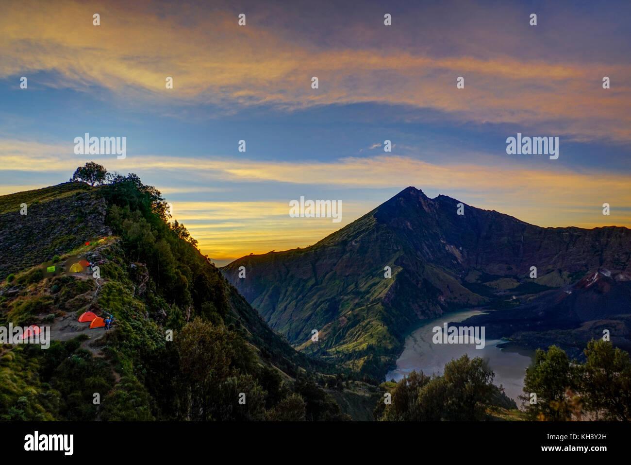 Sunrise Mount Rinjani vulcano with tents Lombok Indonesia - Stock Image