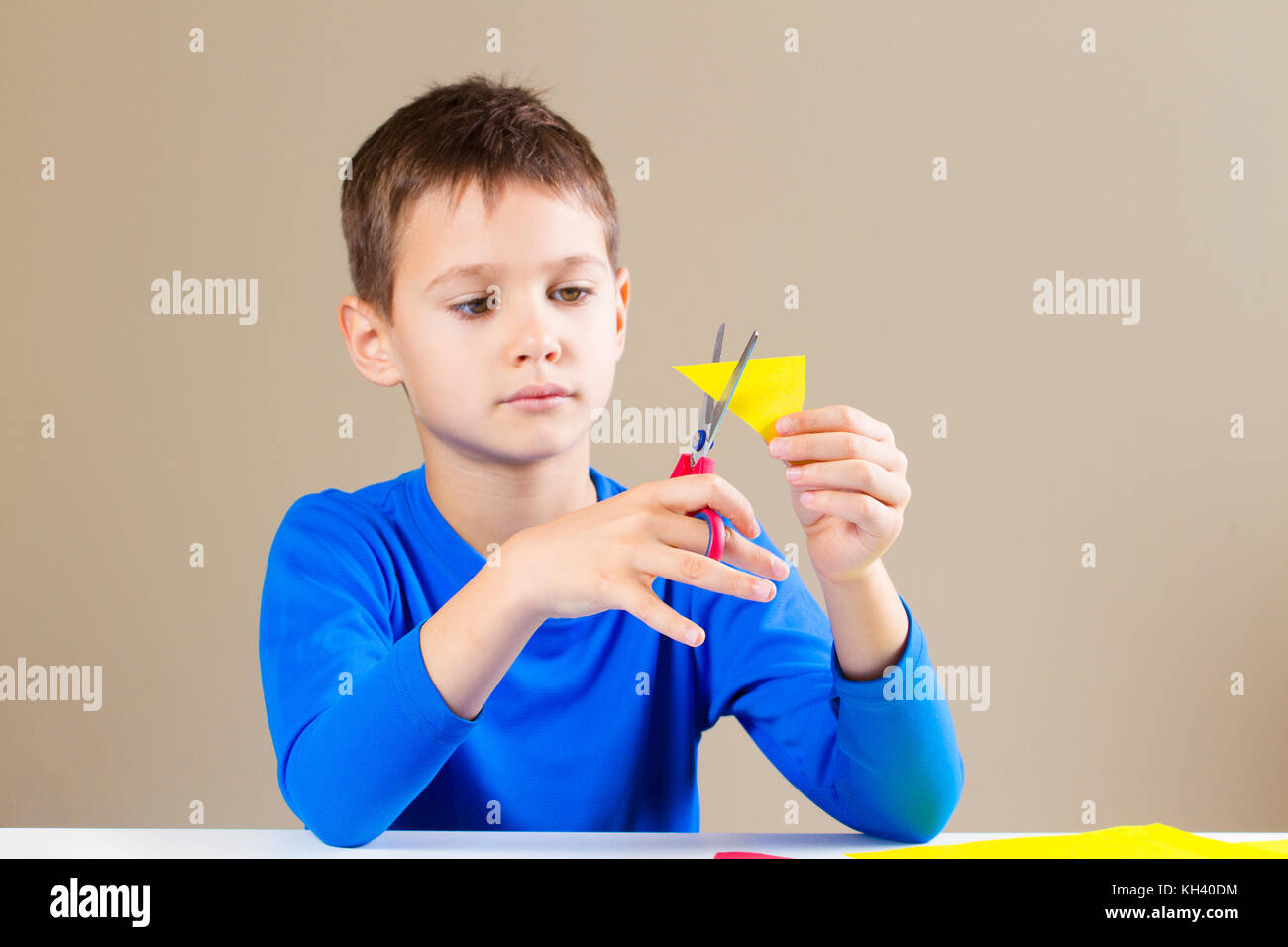 Boy cutting colored paper with scissors - Stock Image