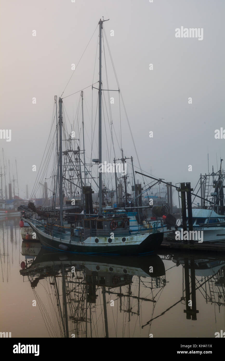 Fishing boats and pleasure craft in Steveston on a foggy morning in Richmond, British Columbia Stock Photo