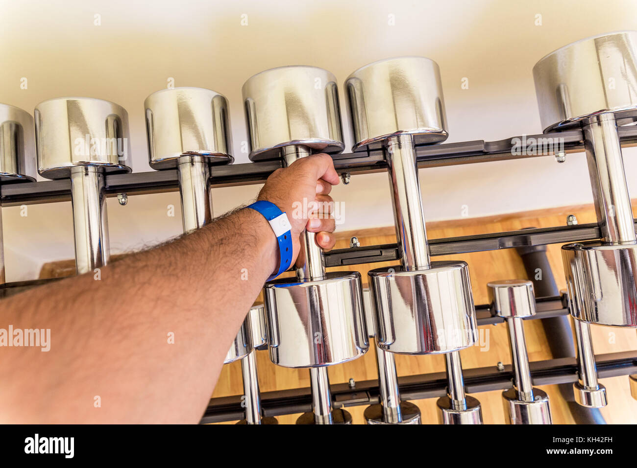 Point of view grabbing dumbbell at the gym - Stock Image