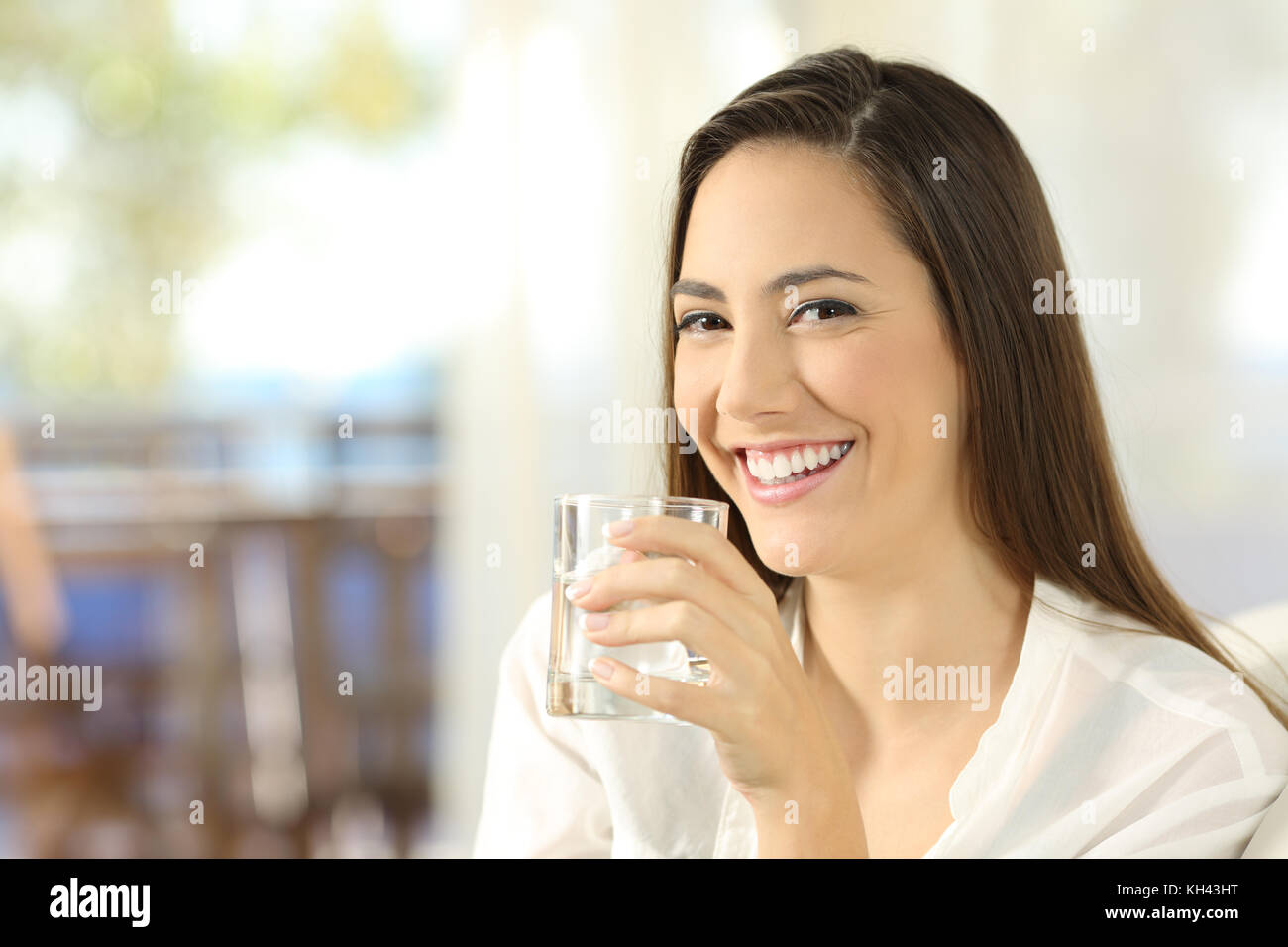 Portrait of a happy woman holding a glass of water and looking at camera sitting on a sofa in the living room at - Stock Image
