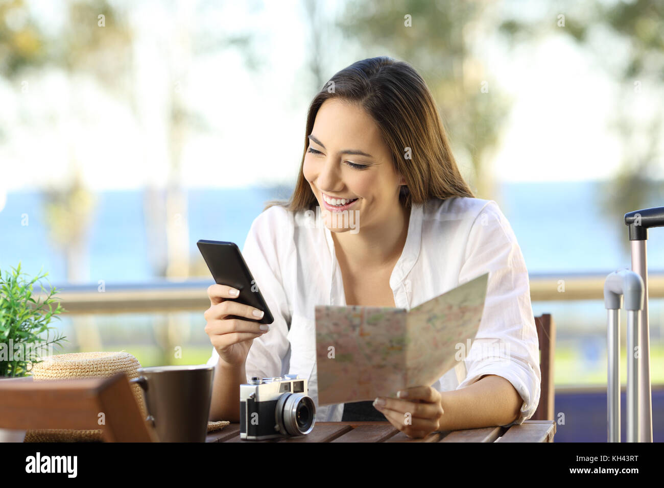 Front view portrait of a tourist searching information on line in a smart phone and a map on vacations in an hotel - Stock Image