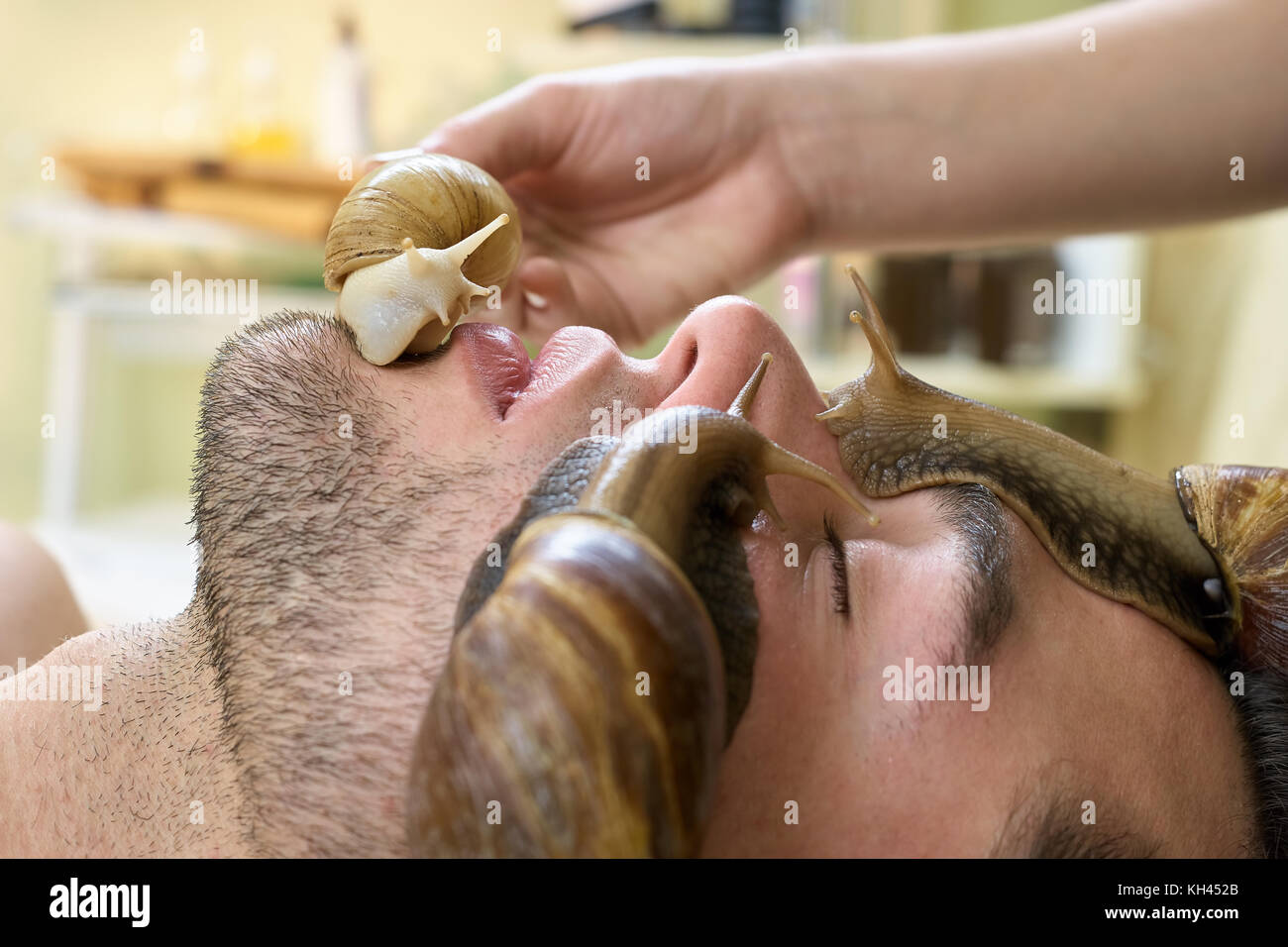 Snails on handsome man face close up. Cleaning and peeling of young man face in spa salon. Modern cosmetological - Stock Image