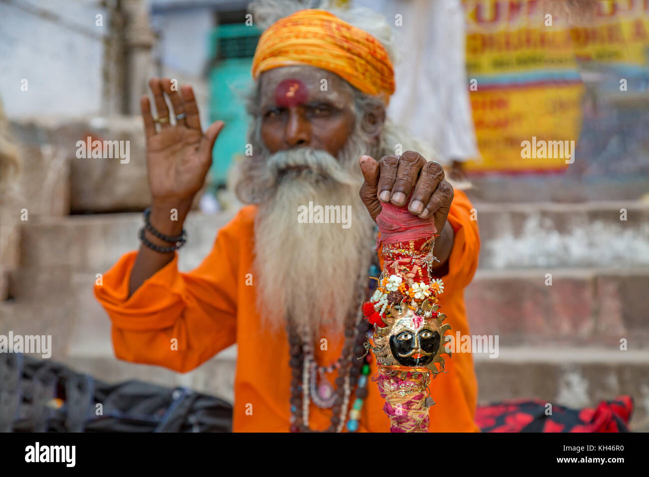 Sadhu baba pose raising the blessing hand at the Ganga river bank in Varanasi, India. - Stock Image