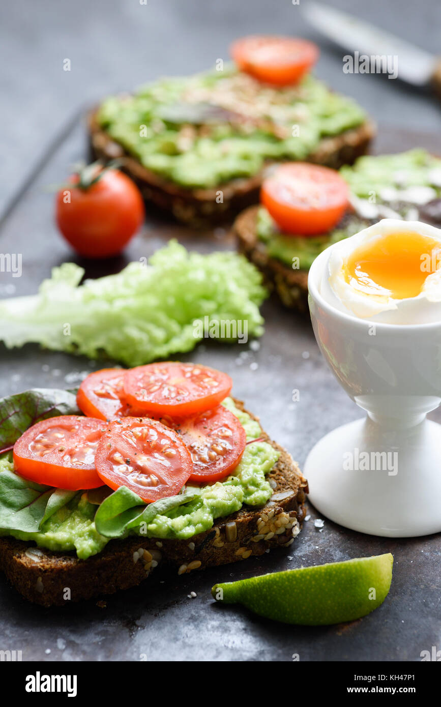 Avocado toast with spinach, tomato and boiled egg. Healthy green veggie open sandwich. Selective focus - Stock Image