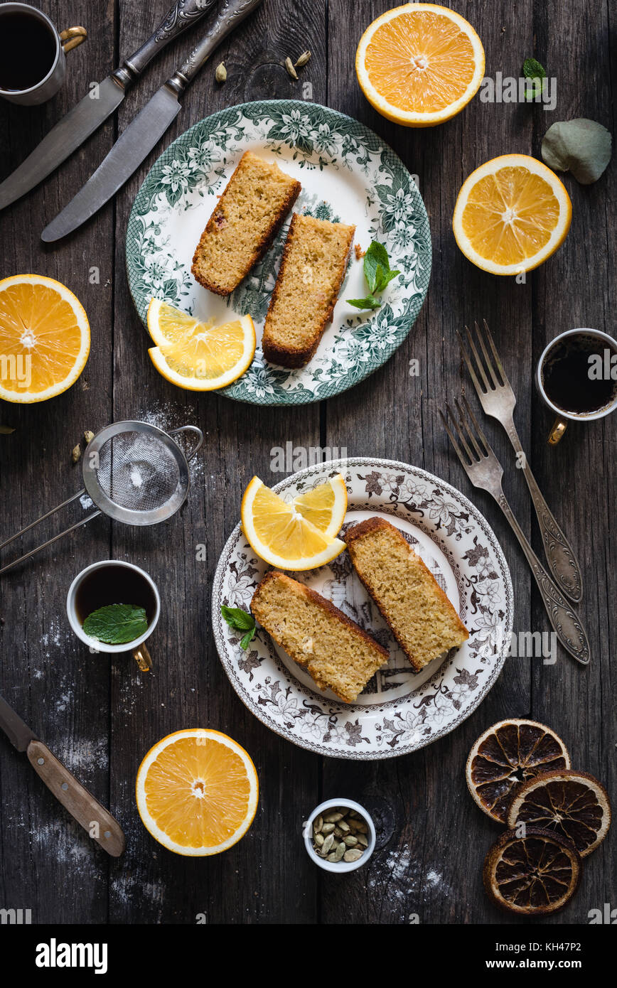 Orange cake served on vintage plate on rustic wooden table background. Food still life. Top view, vertical composition Stock Photo