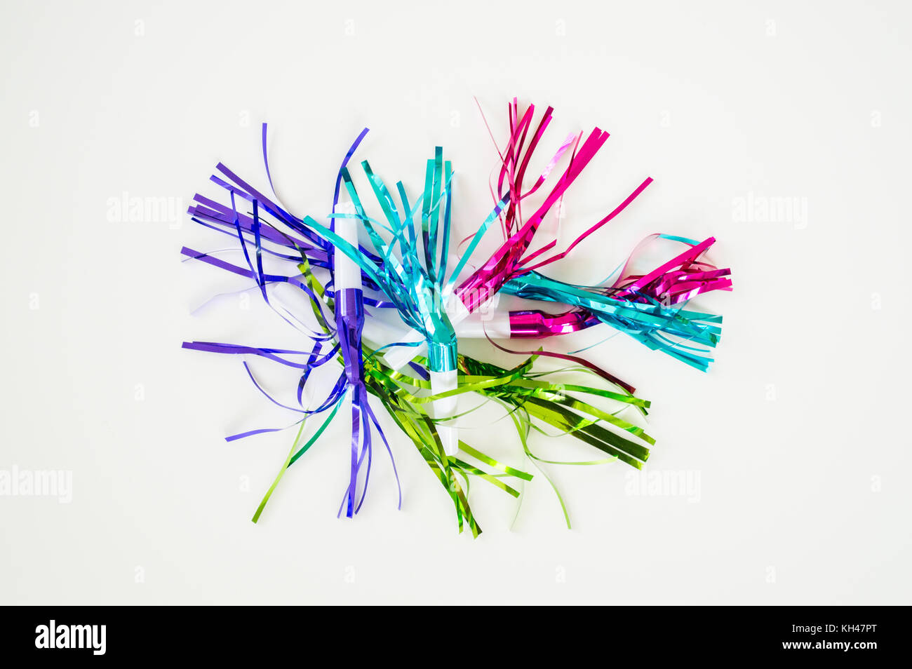 colorful party blowouts and noisemakers with streamers isolated on a solid background - Stock Image
