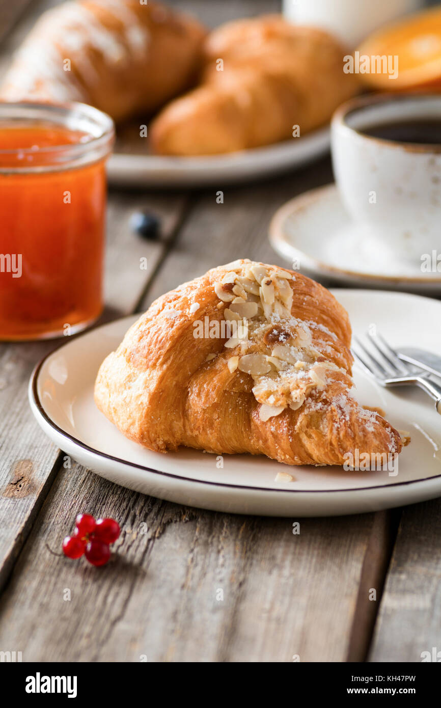 Croissant, jam and coffee on wooden table. Continental breakfast, lunch or brunch in cafe. Closeup view - Stock Image