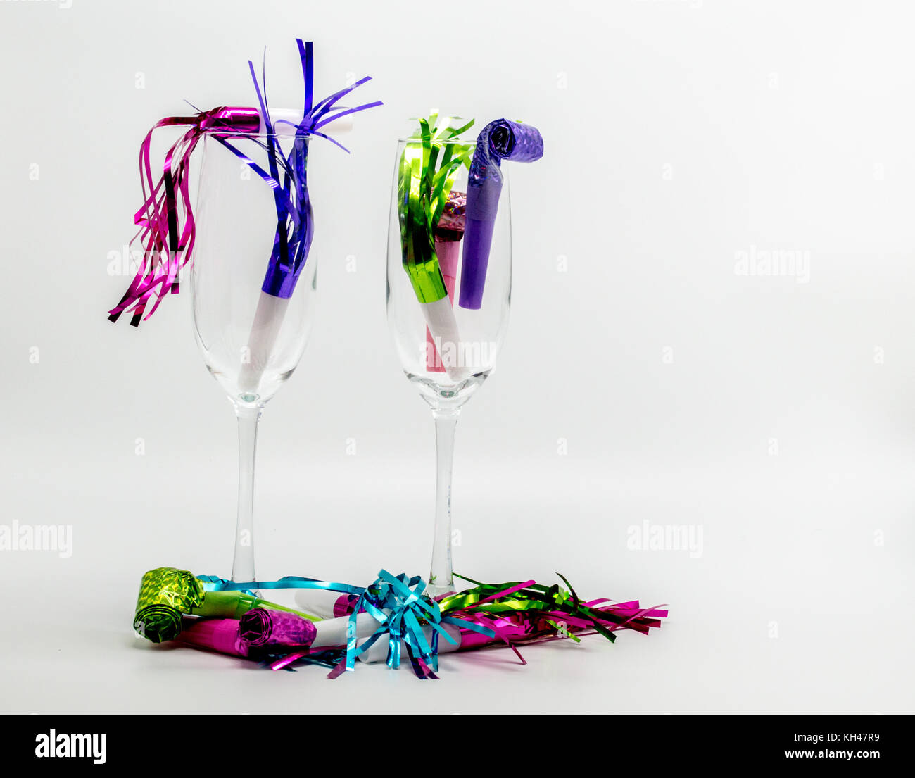 The morning after-2 champagne flutes filled with colorful New Years Eve noisemakers isolated on a solid background - Stock Image