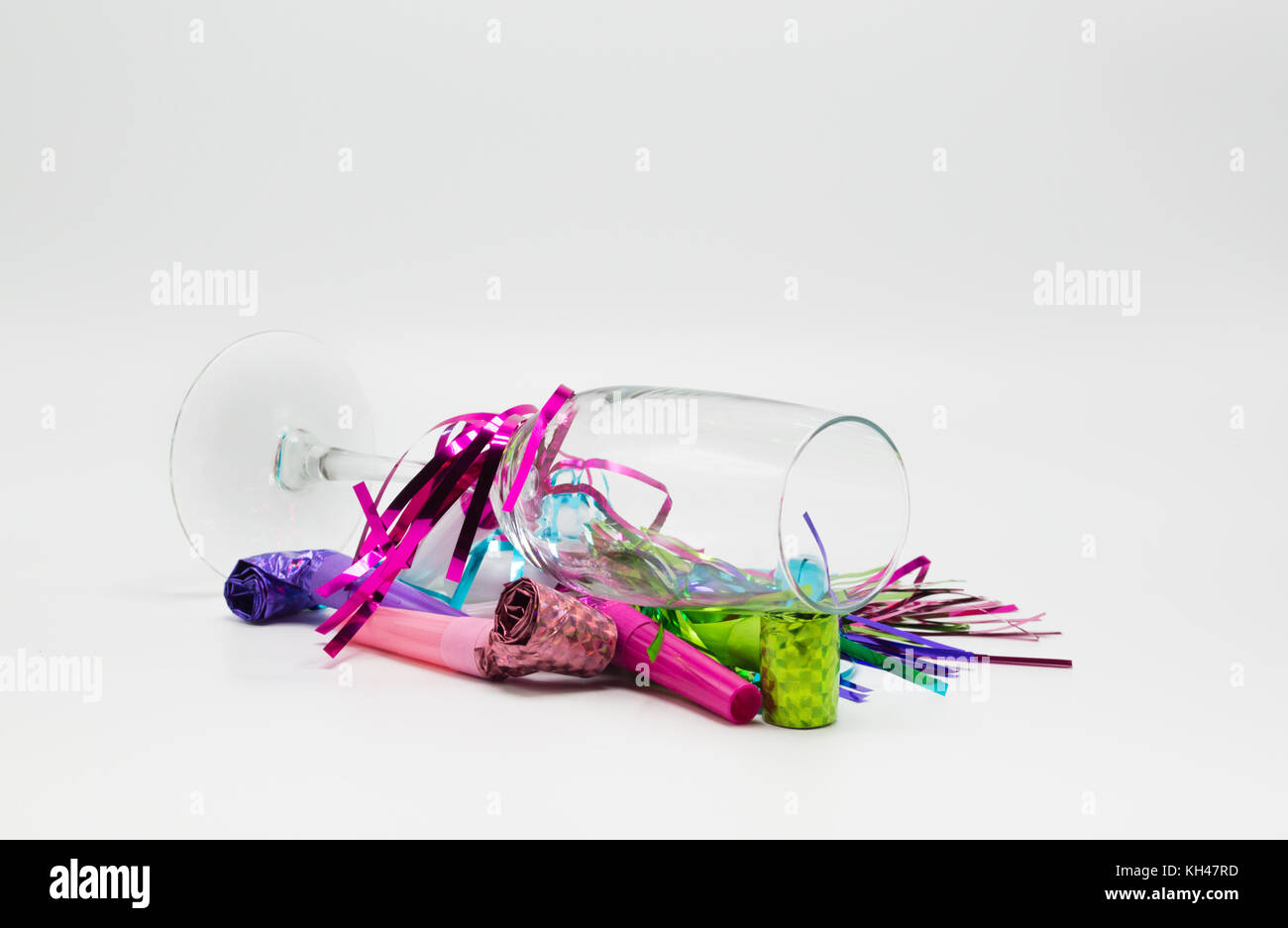 The morning after-champagne flute tipped over and covered with colorful New Years Eve noisemakers isolated on a - Stock Image