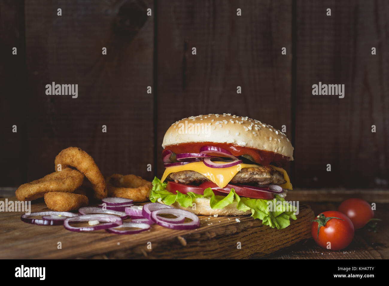Cheeseburger and onion rings on wooden cutting board over wooden background. Closeup view with copy space for text - Stock Image