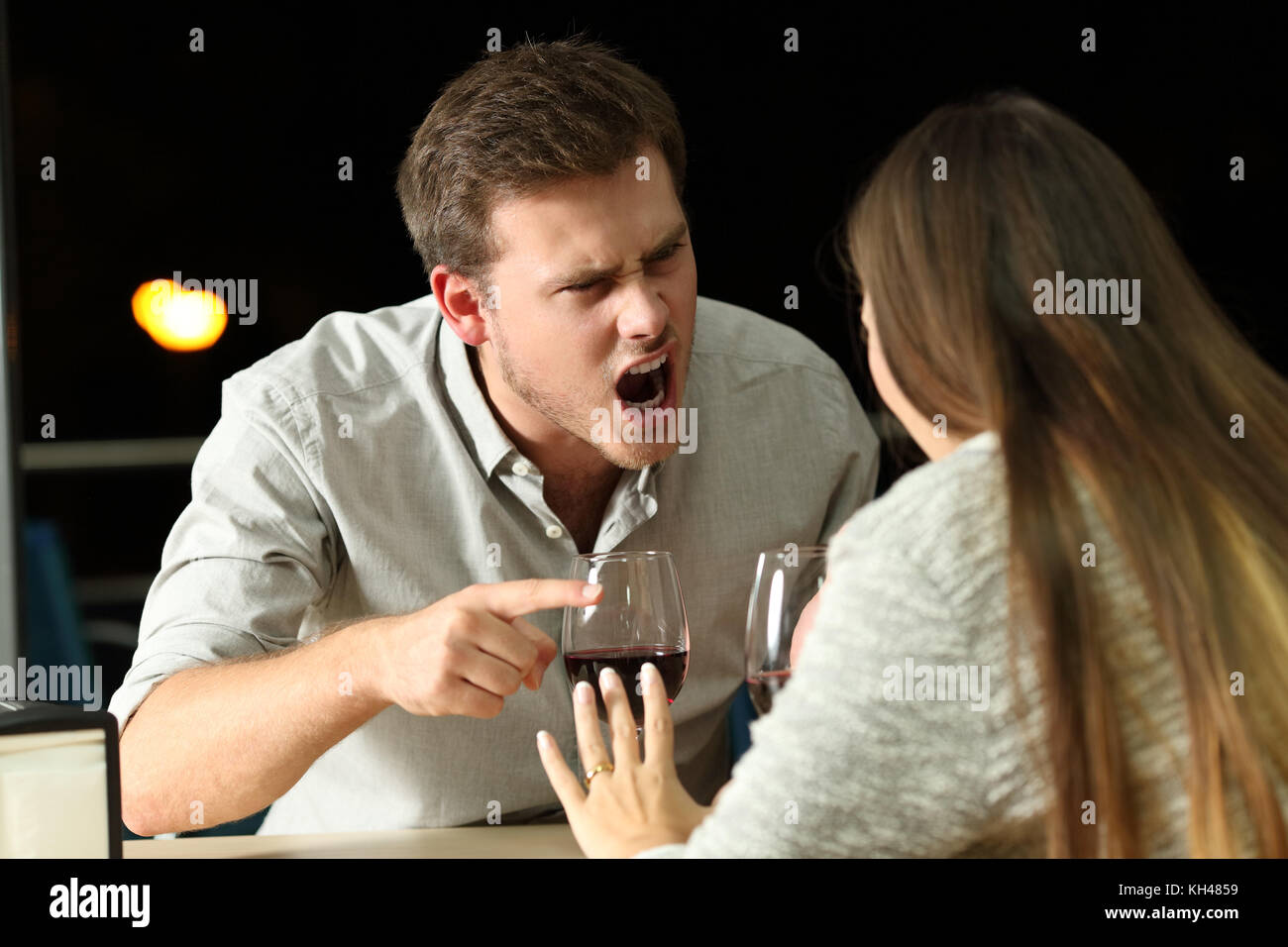 Angry couple arguing furiously in a bar at night - Stock Image
