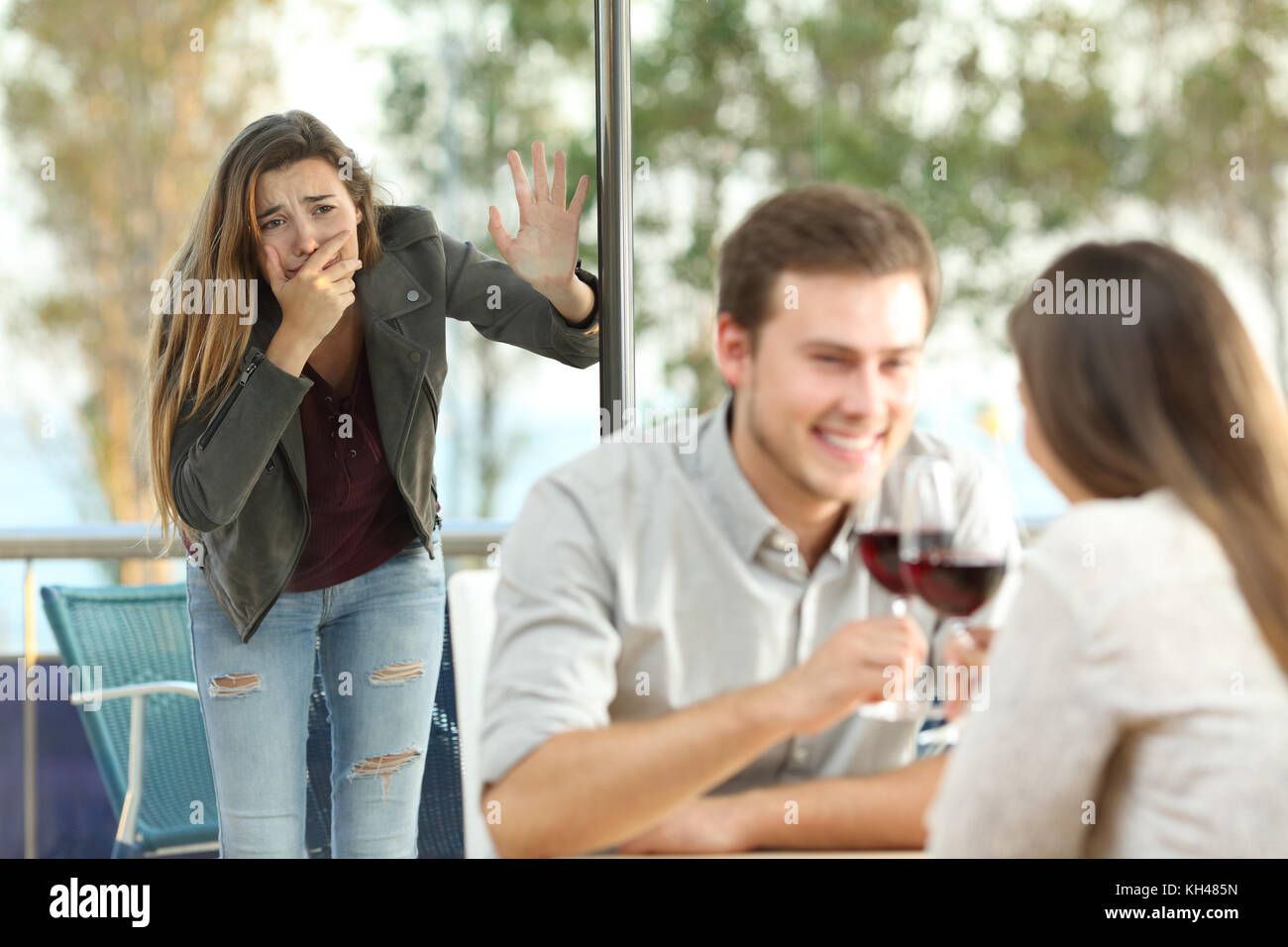 Cheater caught by his sad girlfriend dating with another girl in a coffee shop - Stock Image