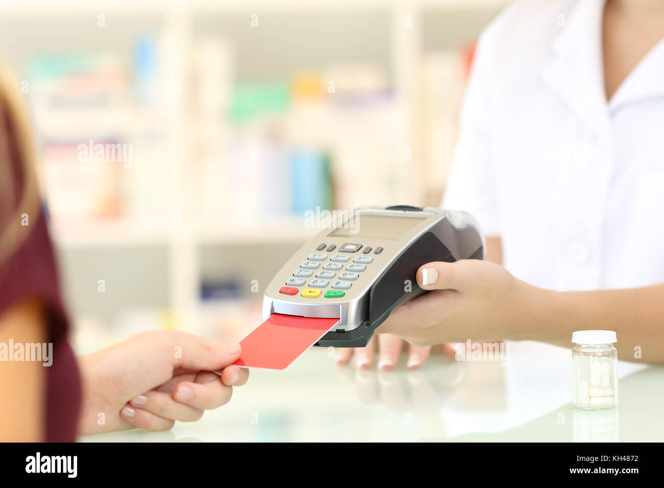 Close up of a pharmacist hands charging with credit card reader on a counter in a pharmacy - Stock Image