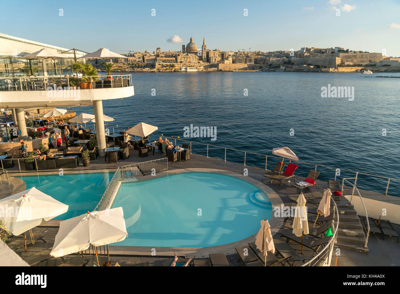 Pool und Restaurant des Hotel Fortina vor der Stadtansicht von Valletta, Malta  |  Hotel Fortina Pool, Terrace Restaurant - Stock Image
