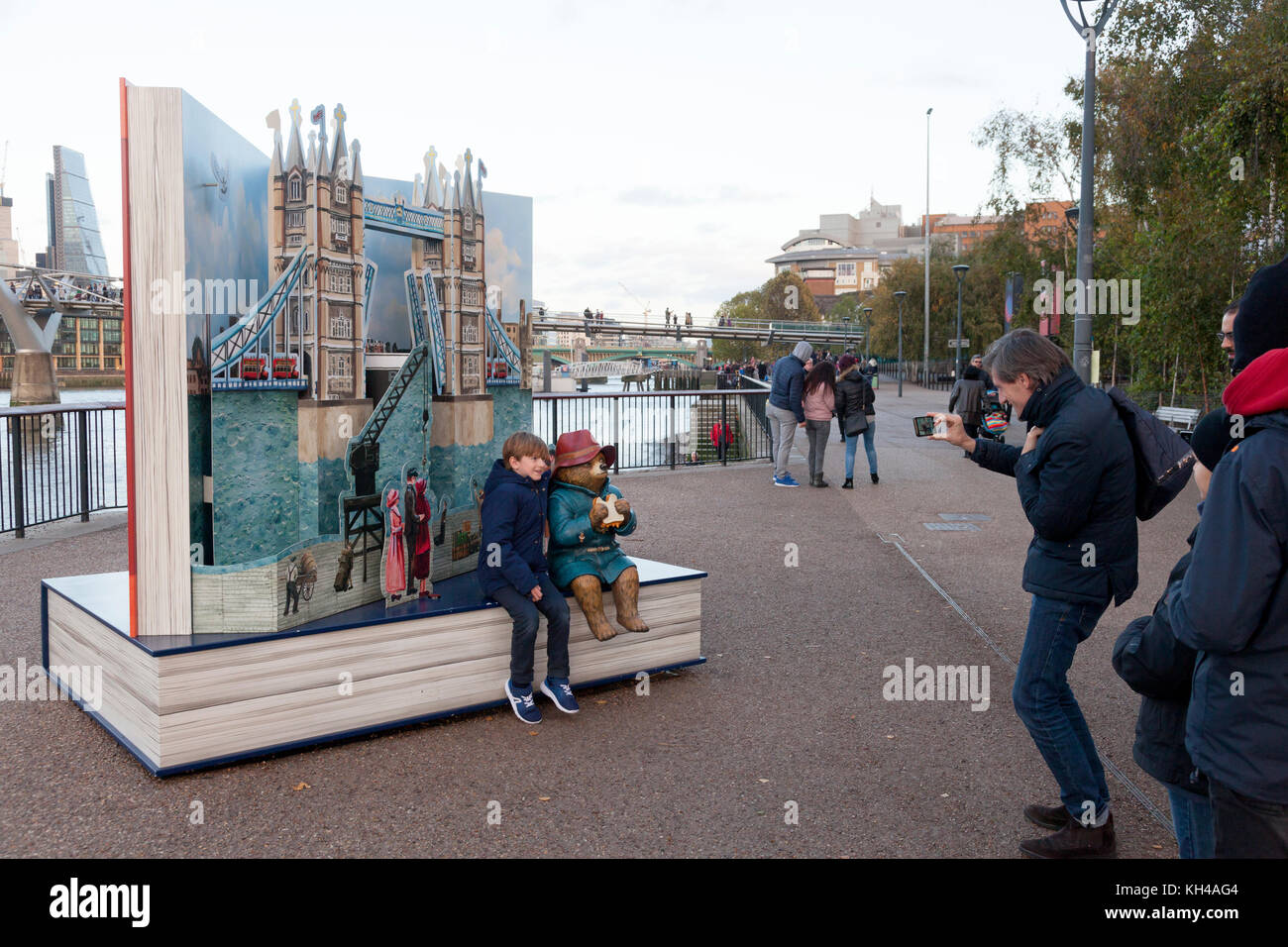 Child being photographed with Paddington Bear beside the Thames at Bankside, London - Stock Image
